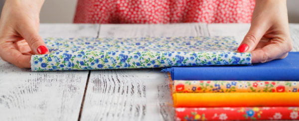 person holding colourful printed fabric